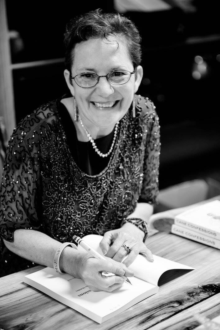 Professional black and white picture of Amy Bovaird Author signing a book wearing a beautiful, happy smile and a braille inscribed bracelet.