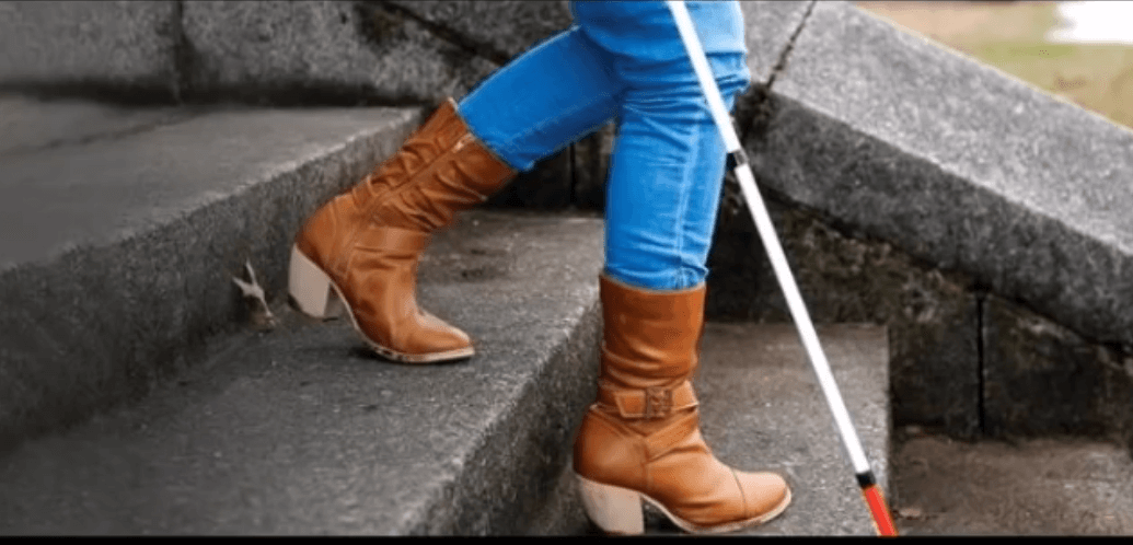 A closeup image of Amys boots and cane walking down steps for The White Cane Song Video Post