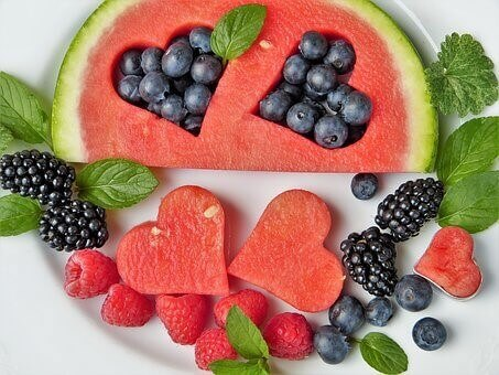 picture of juicy seasonal fruits - watermelon cut in heart shapes, black and red raspberries, blueberries