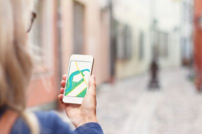 woman walking with aid of GPS app on phone