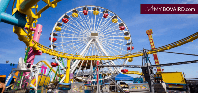 colorful carnival amusement park midway with rollercoaster ferris wheel and other rides
