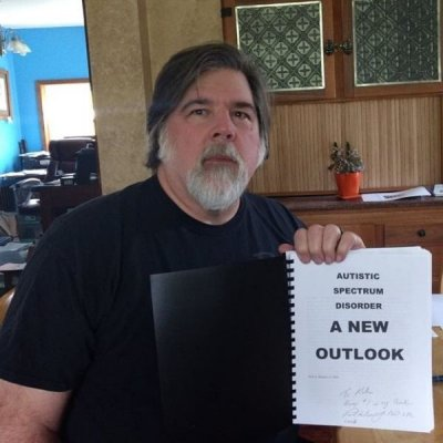 image of Dr Paul Bensur holding his book, A New Outlook