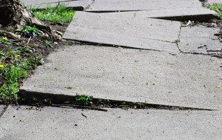 walking down a broken and cracked sidewalk with Retinitis Pigmentosa