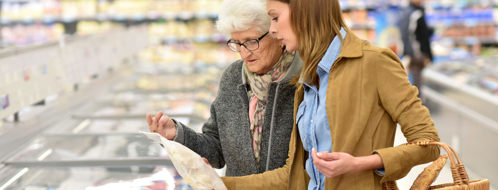 young woman helping an elderly woman read packages in the grocery store