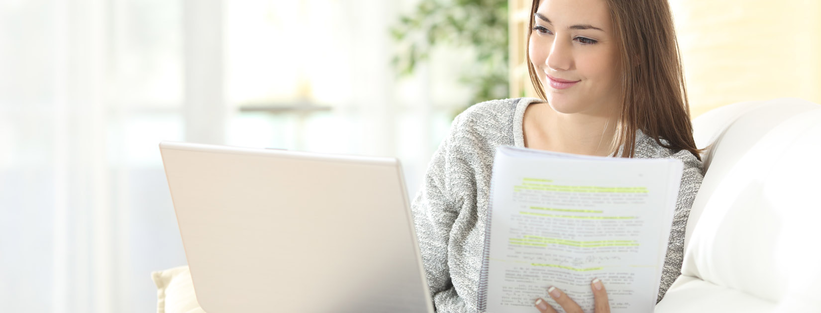woman sitting on couch with laptop and highlighted papers taking a virtual class